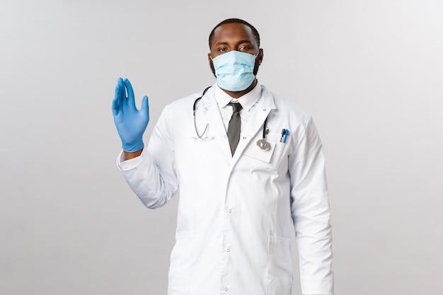 Retrato médico afroamericano en uniforme blanco.