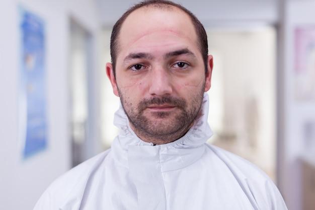 Retrato de médico agotado en la oficina mirando a la cámara con traje de ppe sin protector facial sentado en una silla en la sala de espera