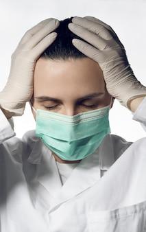 Retrato de médico cansado en mascarilla quirúrgica y guantes con los ojos cerrados