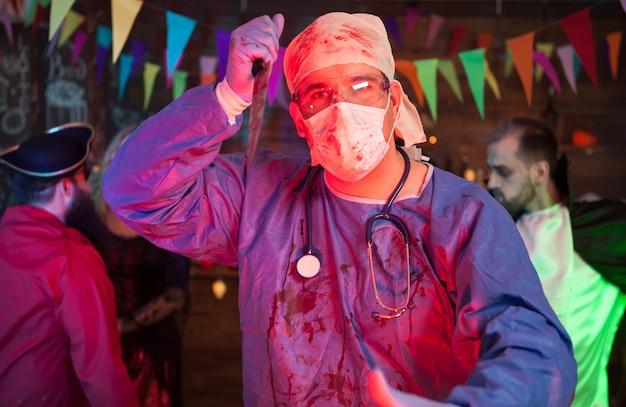 Retrato de médico espeluznante con un cuchillo en la mano mirando a la cámara en una celebración de halloween. hombre disfrazado de drácula en el fondo.
