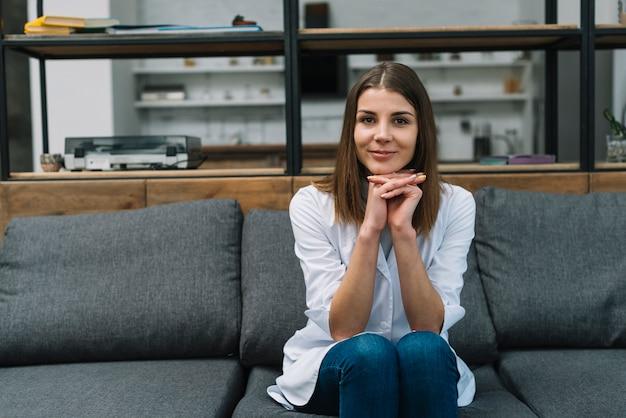 Retrato de un médico femenino sentado en el sofá gris con la mano entrelazada