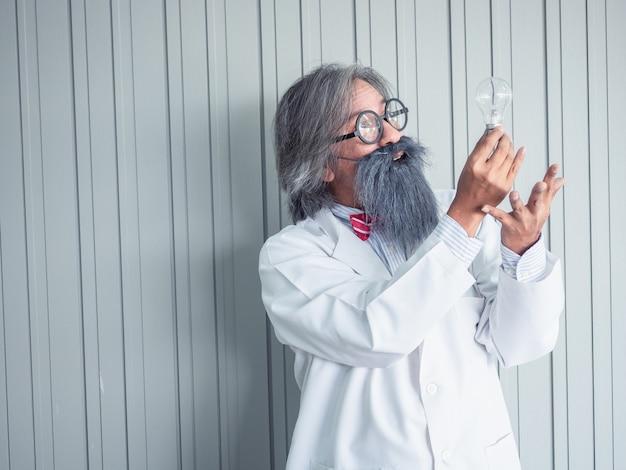 Retrato de un médico frente a un fondo gris grunge con bombilla