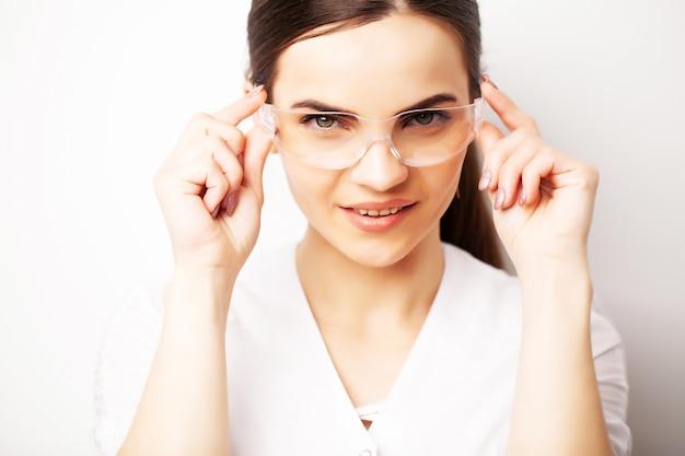 Retrato de un médico con gafas y una bata médica blanca mirando a la cámara.