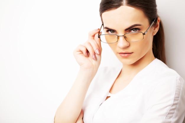 Retrato de un médico con gafas y una bata médica blanca mirando directamente