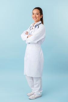 Retrato de un médico joven alegre feliz posando aislado sobre pared azul con estetoscopio.