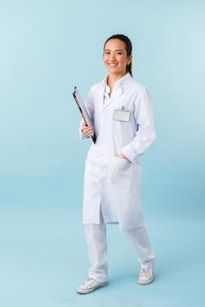 Retrato de un médico joven alegre posando aislado sobre pared azul con portapapeles.