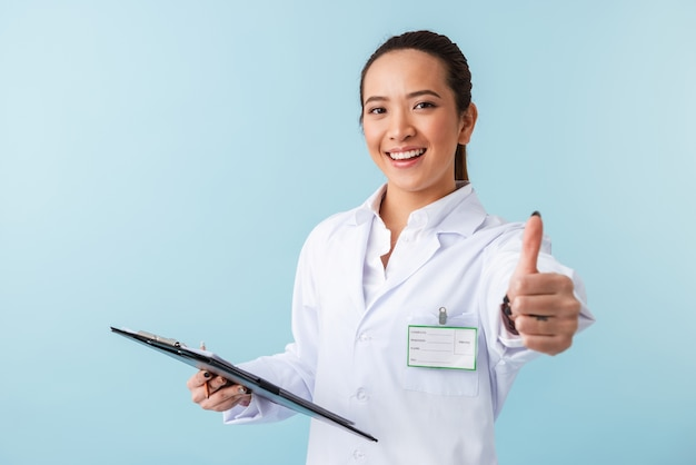 Retrato de un médico joven alegre posando aislado sobre la pared azul sosteniendo el portapapeles mostrando los pulgares para arriba.