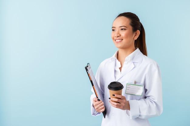 Retrato de un médico joven alegre posando aislado sobre la pared azul sosteniendo el portapapeles y tomando café.