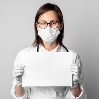 Retrato de médico con máscara quirúrgica con papel