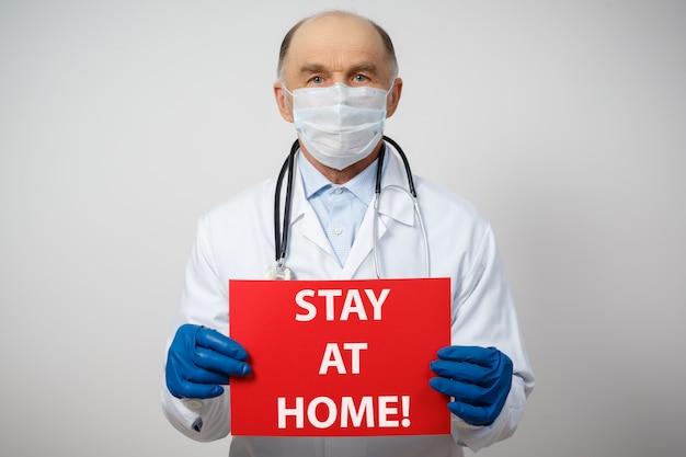 Retrato de un médico masculino en una máscara protectora médica y guantes con un cartel de estancia en casa.