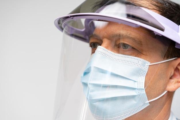 Retrato de médico de mediana edad con protector facial cerrar