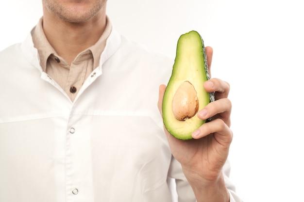 Retrato de médico nutricionista masculino sonriente positivo con aguacate. piel sana y hermosa, comida dietética, concepto de pérdida de peso