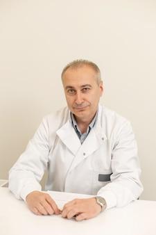 Retrato de un médico profesional masculino en una bata blanca sentado en una mesa