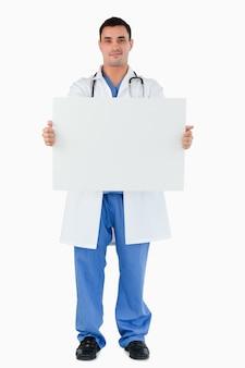 Retrato de un médico sosteniendo un panel en blanco