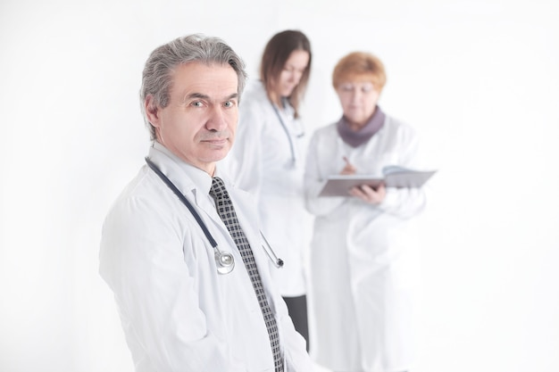 Retrato de un médico terapeuta exitoso sobre fondo borroso de colegas