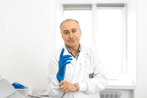 Retrato de un médico urólogo poniéndose guantes médicos antes de examinar a un paciente