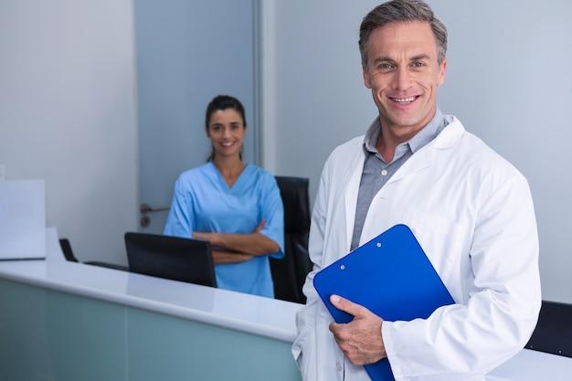 Retrato de médicos sonrientes de pie contra la pared