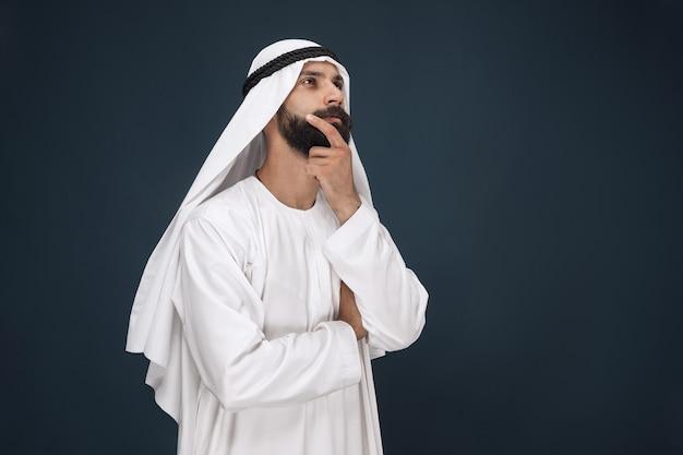 Retrato de medio cuerpo del empresario saudí árabe en la pared azul oscuro del estudio