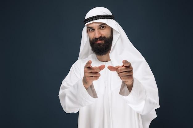 Retrato de medio cuerpo del empresario saudita árabe en estudio azul oscuro