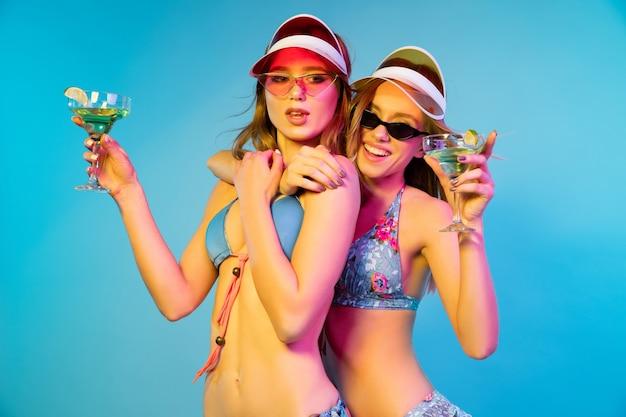 Retrato de medio cuerpo de hermosas chicas jóvenes aislado sobre fondo azul en luz de neón.