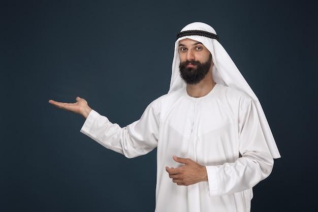Retrato de medio cuerpo del hombre saudí árabe en el espacio azul oscuro. modelo masculino joven sonriendo y señalando