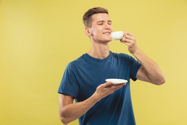Retrato de medio cuerpo del joven caucásico sobre fondo amarillo de estudio. hermoso modelo masculino en camisa azul. concepto de emociones humanas, expresión facial. disfrutando tomando café o té.