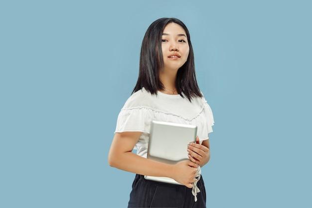 Retrato de medio cuerpo de la joven coreana en estudio azul