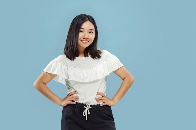 Retrato de medio cuerpo de la joven coreana sobre fondo azul.