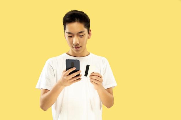 Retrato de medio cuerpo del joven coreano en amarillo