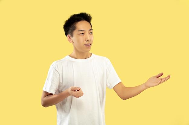 Retrato de medio cuerpo del joven coreano en la pared amarilla
