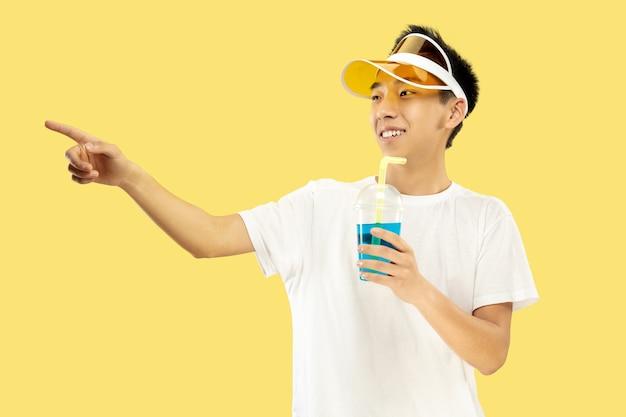 Retrato de medio cuerpo del joven coreano sobre fondo amarillo de estudio. modelo masculino con camisa blanca y gorra amarilla. beber cóctel. concepto de emociones humanas, expresión, verano, vacaciones, fin de semana.