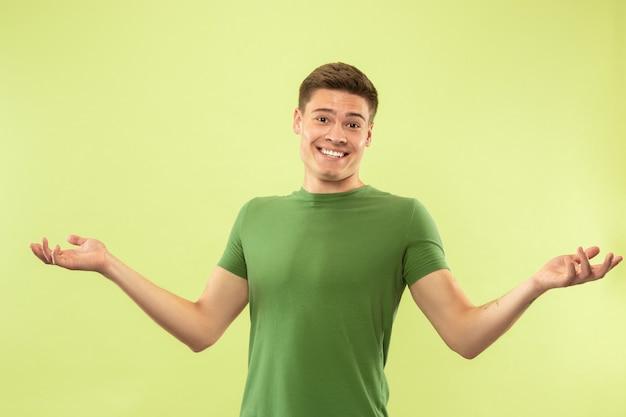 Retrato de medio cuerpo del joven en la pared verde del estudio