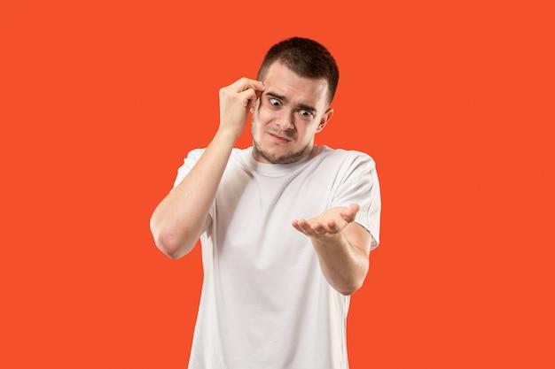 Retrato de medio cuerpo masculino hermoso aislado en el fondo anaranjado del estudio. el joven sorprendido emocional