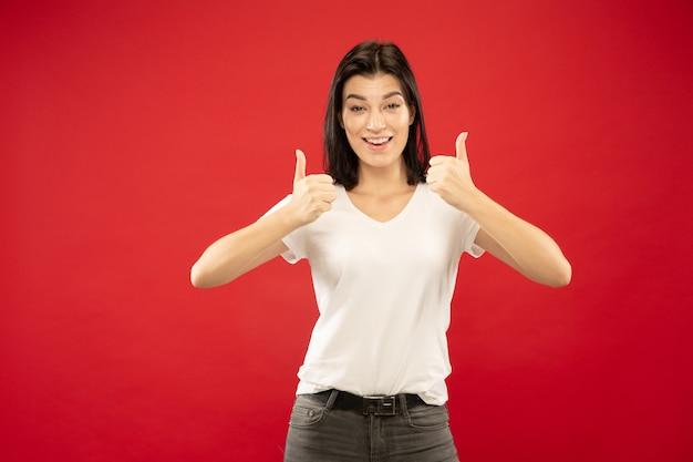 Retrato de medio cuerpo de la mujer joven caucásica sobre fondo rojo de estudio. modelo de mujer hermosa en camisa blanca. concepto de emociones humanas, expresión facial. mostrando el signo de agradable, genial.