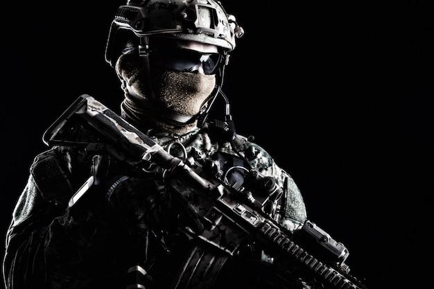 Retrato de medio cuerpo de soldado de las fuerzas especiales en uniformes de campo con armas, retrato en negro