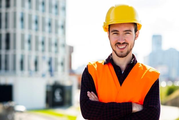Retrato medio del trabajador de construcción que mira la cámara