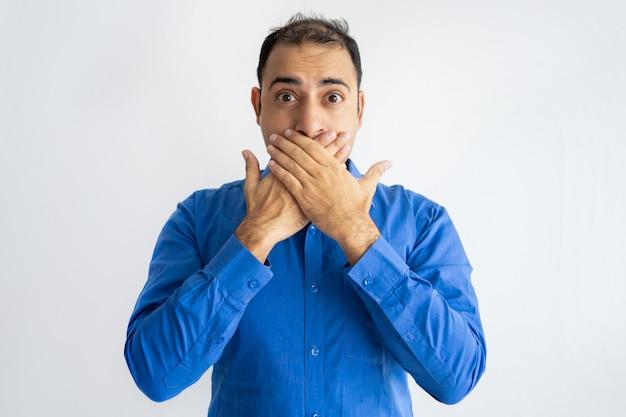 Retrato de miedo mediados de hombre de negocios adulto que cubre la boca