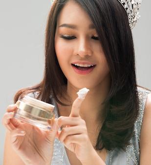 Retrato de miss pageant beauty contest lentejuelas evening crown, moda de mujer asiática maquillaje revisión de estilo de cabello negro que prueba un hermoso suero de crema juvenil en la cara, iluminación de estudio, fondo gris dramático