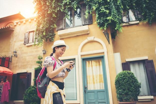 Retrato de la mochila joven de la mujer del inconformista que viaja tomando la foto en urbano.