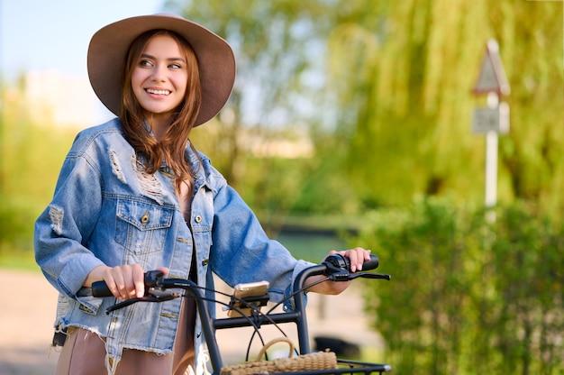 Retrato de moda al aire libre de dama elegante montando su bicicleta de alquiler con chaqueta vaquera y sombrero de paja. disfruta del día de verano, posando en la calle con árboles.