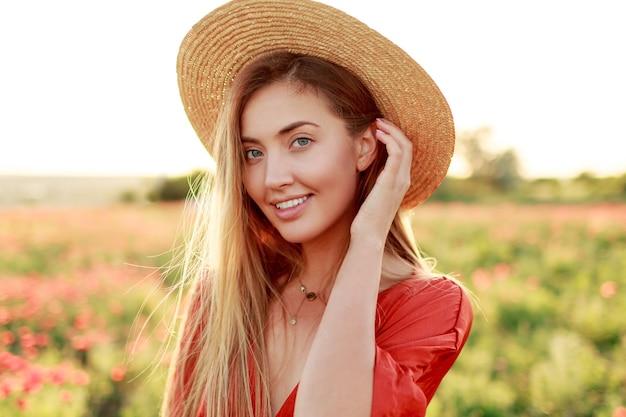 Retrato de moda al aire libre de impresionante mujer rubia posando mientras camina en el increíble campo de amapolas en una cálida noche de verano. con sombrero de paja, bolso de moda y vestido rojo.