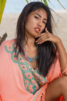 Retrato de moda al aire libre de mujer asiática en playa tropical, ella se está relajando, soñando. llevando joyas, brazalete y collar.