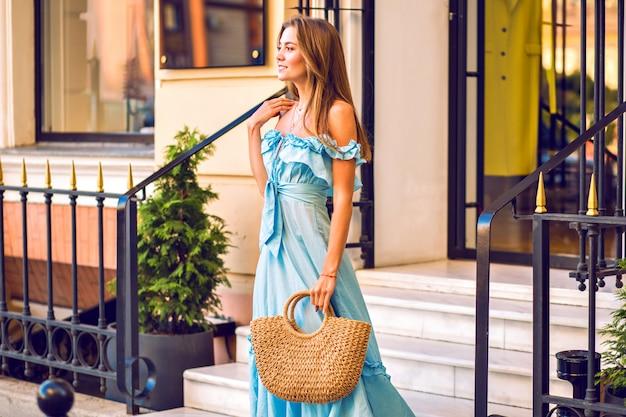 Retrato de moda al aire libre de mujer elegante con vestido azul de moda con volantes