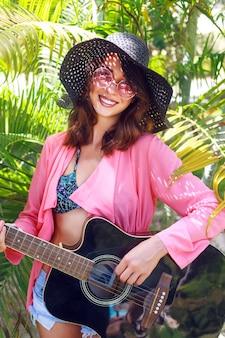 Retrato de moda al aire libre de mujer hippie muy sonriente feliz sentado en el césped y sosteniendo la guitarra acústica. país tropical caliente, fondo verde. traje de verano con sombrero y gafas de sol rosas.