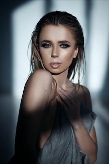 Retrato de moda de arte de una hermosa mujer rubia con maquillaje y cabello mojado.