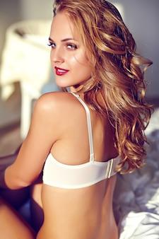 Retrato de moda de la bella y sexy modelo de mujer rubia adulta joven vistiendo lencería erótica blanca posando en luz interior en el amanecer de la mañana