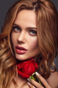 Retrato de moda de belleza de joven rubia modelo con maquillaje natural y piel perfecta con hermosa rosa posando