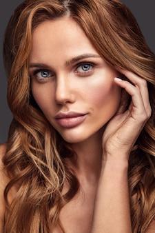 Retrato de moda de belleza de modelo joven rubia con maquillaje natural y piel perfecta posando. tocando su cabello