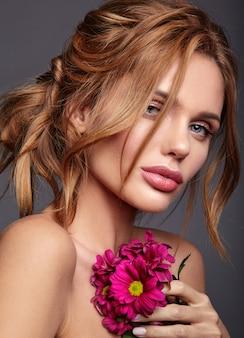 Retrato de moda de belleza de modelo de mujer joven rubia con maquillaje natural y piel perfecta con brillante flor de crisantemo rimson posando