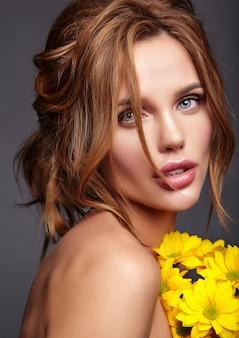 Retrato de moda de belleza de mujer joven rubia modelo con maquillaje natural y piel perfecta con flor de crisantemo amarillo brillante posando